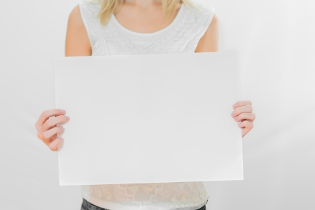 Young beautifull woman posing with white sheet of paper isolated on white background photo