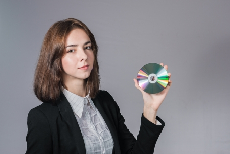 rewrite: Portrait of businesswoman holding the cd disk in her hand isolated on white