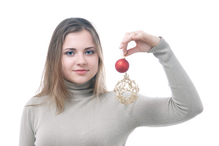 Portrait of girl looking at two christmass toys in her hand - red and gold isolated on white photo