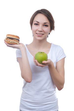 Girl makes choice between apple and hamburger isolated on white photo
