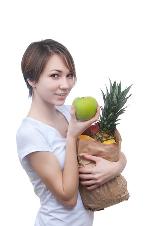 Pretty young girl with package of fruits and green apple isolated on white photo