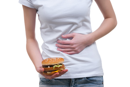 Body of girl with hamburger in the hands massage its stomach isolated on white photo