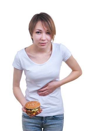 Portrait of girl with hamburger in the hands and strong stomach-ache isolated on white photo