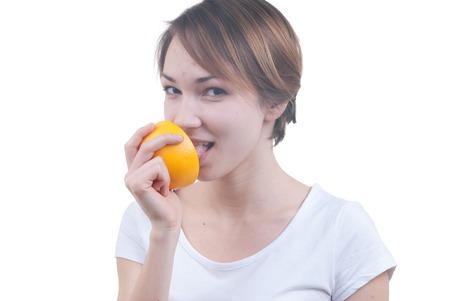 Portrait of girl licking half of grapefruit isolated on white photo