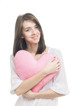 Yoyng smilling girl with valentine pink pillow heart isolated on white background photo