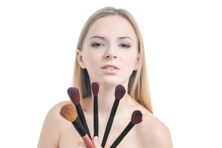 Beauty photo of girl with five makeup brushes isolated on white photo