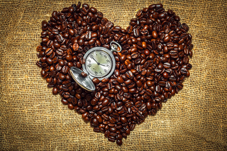 Coffee Heart with clock on it made from beans lying on burlap photo