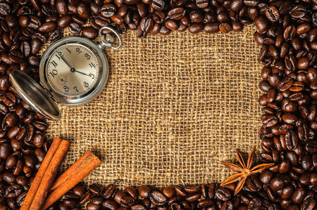 Coffe frame made of beans on burlap with star anise, cinnamon and retro watch