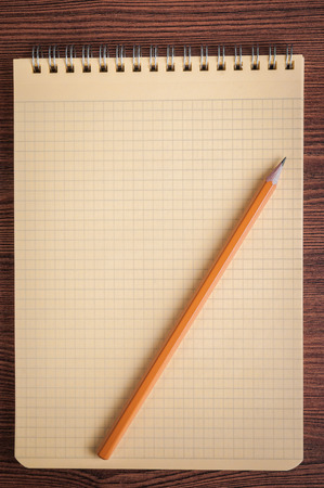 Blank notepad and pencil laying on it on office wooden table