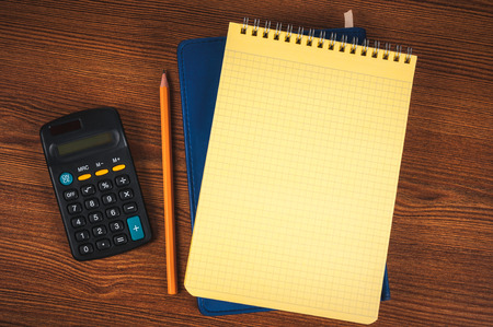 Blank notepads, calculator and pencil laying on it on office wooden table