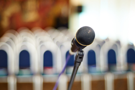 people in a row: close up photo of mikrophone on the business auditory background Stock Photo
