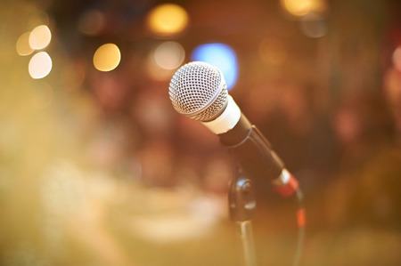 microphone in concert hall or conference room with warm lights in background