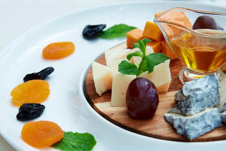 a jar stand: Cheese, grapes, mint, pitcher of oil, prunes and dried apricots are laid out on a wooden board
