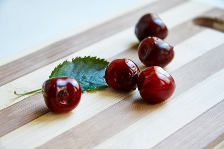 berryes: Photo of cherry berryes and green leaf on the wooden cutting board