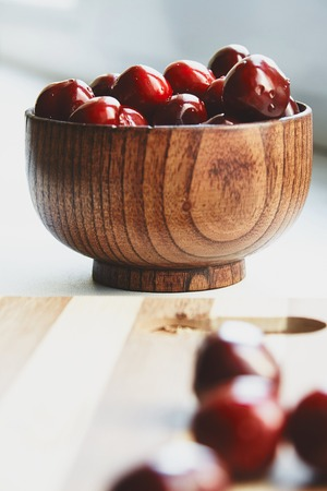 berryes: Photo of cherry berryes in the wooden bowl on the cutting board Stock Photo