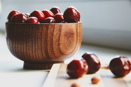 berryes: Photo of cherry berryes in the wooden bowl and green leaf on the cutting board