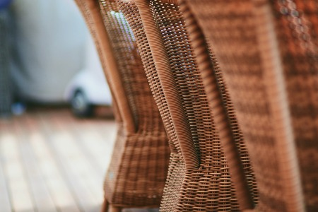 woden: Photo of the backside of four brown woden rattan armchairs in the restaurant