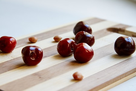 pits: Photo of cherry berries and cherry pits on the wooden cutting board Stock Photo