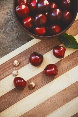 pits: Photo from above of cherry berries in the wooden bowl and green leaf on the wooden cutting board with three pits on the bokeh background Stock Photo
