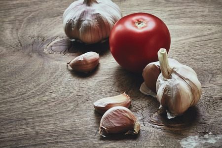 bulb and stem vegetables: From above photo of red tomato on the green stem and three garlic cloves on the wooden table Stock Photo