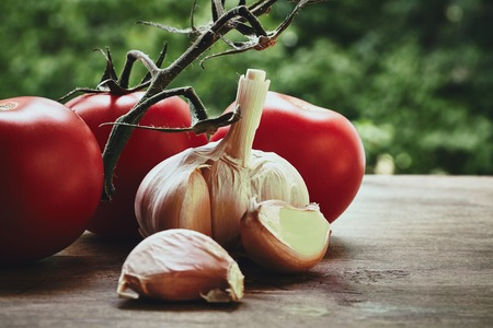 bulb and stem vegetables: Photo of red fresh tomatoes on the green stem garlic bulb and cloves on the blured background