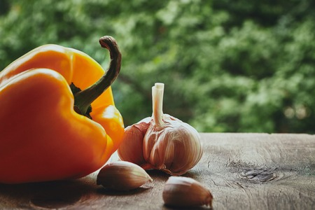 bulb and stem vegetables: Photo of orange pepper, garlic bulb and cloves on the blured background