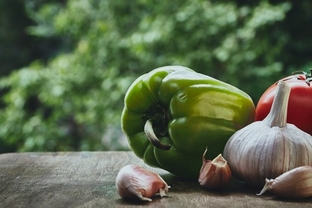 bulb and stem vegetables: Composition with green pepper, red fresh tomatoe with the green stem, garlic bulb and cloves on the blured background