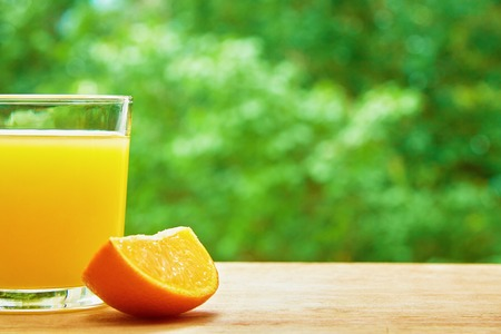 lobule: Photo of glass of orange juice and orange lobule on the wooden table on the green blurred background