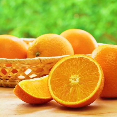 lobule: Orange , half of orange, orange lobule and basket with oranges on the wooden table on the green blurred background Stock Photo