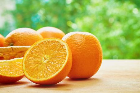 verre de jus d orange: Orange, la moitié d'orange, orange et lobule panier avec des oranges sur la table en bois sur le fond flou vert