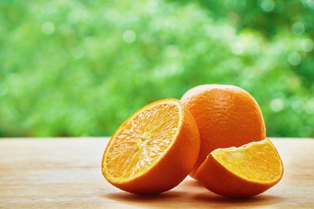 orange: Orange, half of orange and orange lobule on the wooden table on the green blurred background