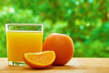 lobule: Orange, glass with orange juice and orange lobule on the wooden table on green blured background