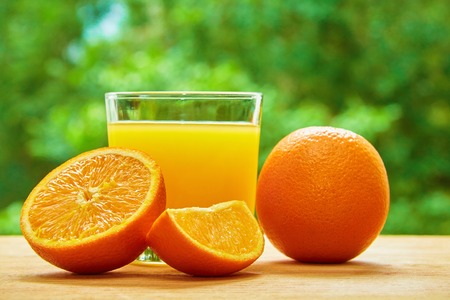 lobule: Glass with orange juice, orange and the half of it and orange lobule on the wooden table on the green blurred background