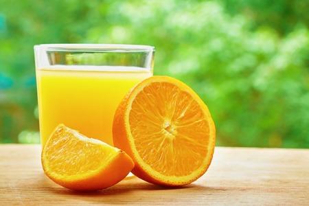 lobule: Photo of glass of orange juice, orange lobule and half of orange on the wooden table on the green blurred background