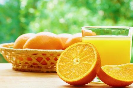 lobule: Glass of orange juice, half of orange, orange lobule and basket with oranges on the wooden table on the green blurred background