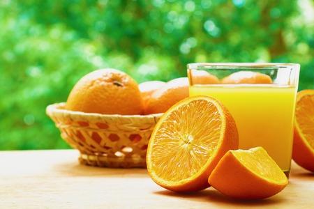 lobule: Glass of orange juice, two halves of orange, orange lobule and basket with oranges on the wooden table on the green blurred background