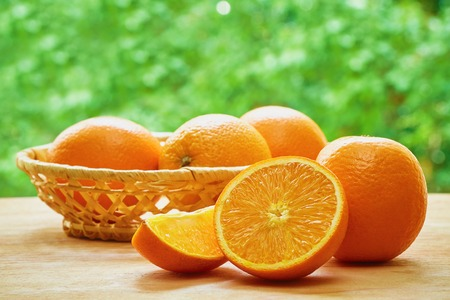 Orange, half of orange, orange lobule and basket with oranges on the wooden table on the green blurred background
