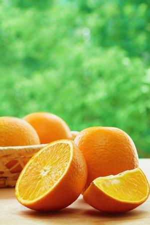 lobule: Orange, half of orange, orange lobule and basket with oranges on the wooden table on the green blurred background