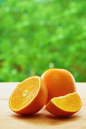 lobule: Orange, half of orange and orange lobule on the wooden table on the green blurred background