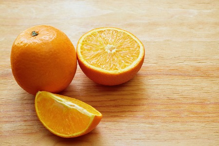 orange slices: Orange, half of orange and orange lobule on the wooden table