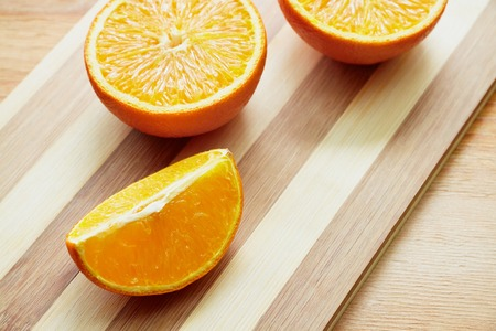 lobule: Two halves of orange and orange lobule on the wooden cutting board