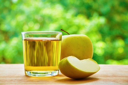 lobule: Apple, glass with apple juice and apple lobule on the wooden table on green blurred background Stock Photo