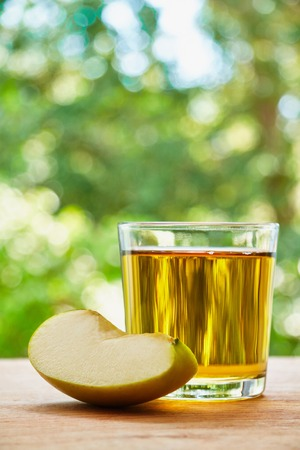 lobule: Glass with apple juice and apple lobule on the wooden table on green blurred background