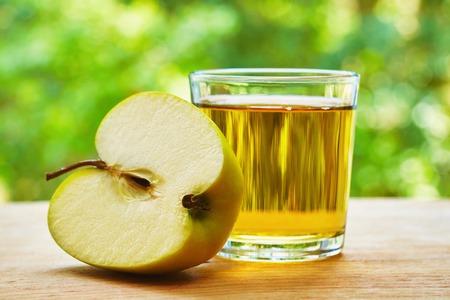 vaso de jugo: Vidrio con el jugo de manzana y manzana partida en dos en la mesa de madera sobre fondo verde borrosa