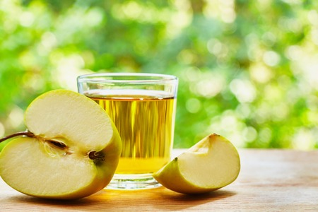 lobule: Glass with apple juice. halved apple and apple lobule on the wooden table on green blurred background