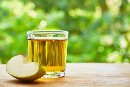 juice glass: Glass with apple juice and apple lobule on the wooden table on green blurred background