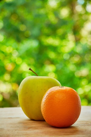 sweet pulp: Photo of orange and apple on the wooden table on green blured background
