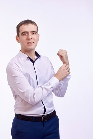 young  cuffs: Young smilling man in lilac shirt standing on on white background buttoning on the sleeve of his shirt Stock Photo