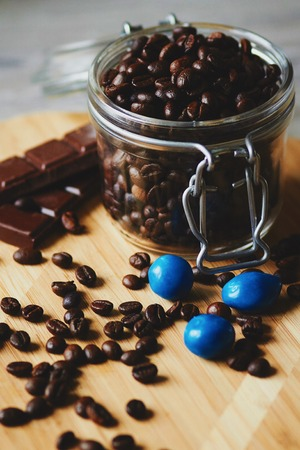 sweetmeats: Candies, chocolate and coffee beans in a jar on the wooden table Stock Photo