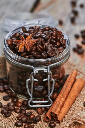 seed pots: Coffee beans and star anise in jar with cinnamon on sackcloth on the wooden table Stock Photo